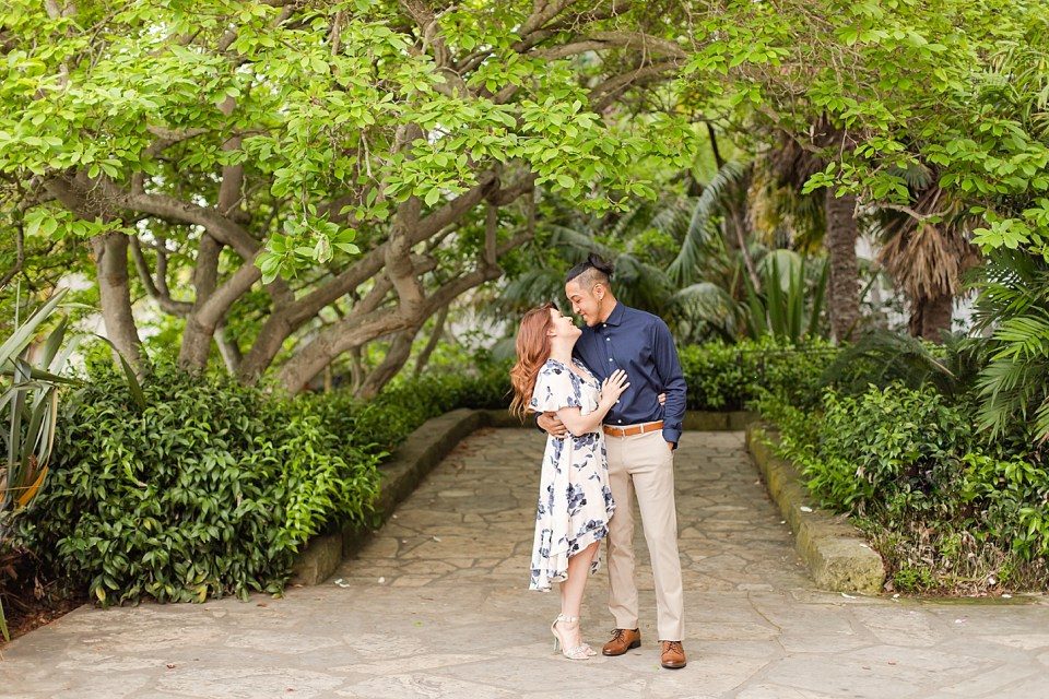 Danielle is wearing a white dress with high heels and Ray is wearing a blue button up shirt and khaki pants with light brown shoes. The couple is smiling at each other and her hand is on his chest. The couple is standing underneath green trees and branches on a path at the Santa Barbara Courthouse in Santa Barbara, California.