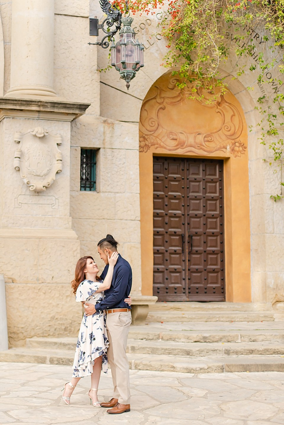 The bride and groom to be standing in front of the Santa Barbara Courthouse with a large brown door and lantern with bougainvillea hanging down.