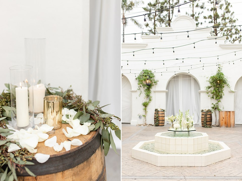 Wine barrel with white flower petals and three lit candles. A second photo of the altar before anyone is there.