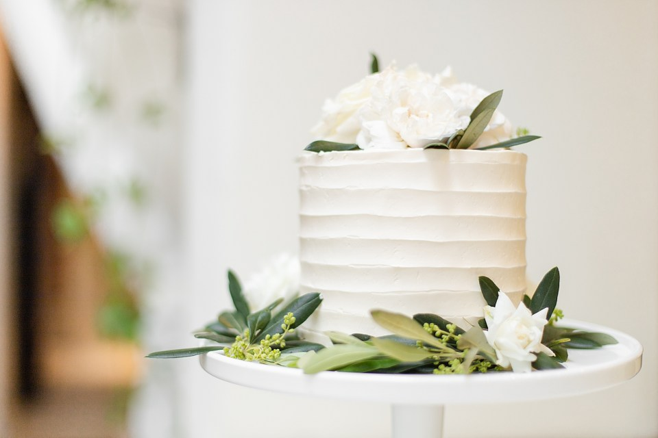 The couple's simple white wedding cake with green leaves and a few white flowers around it.