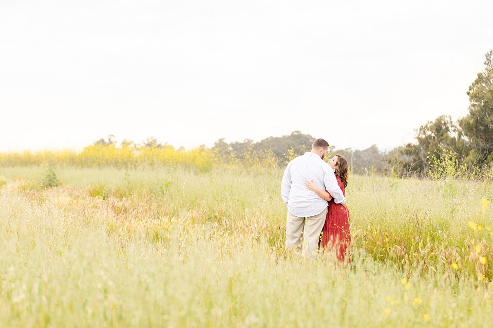 Maddy smiling up at Brian as he smiles down towards her while they hold each other closely in a field of yellow flowers during their Ellwood Bluffs engagement session