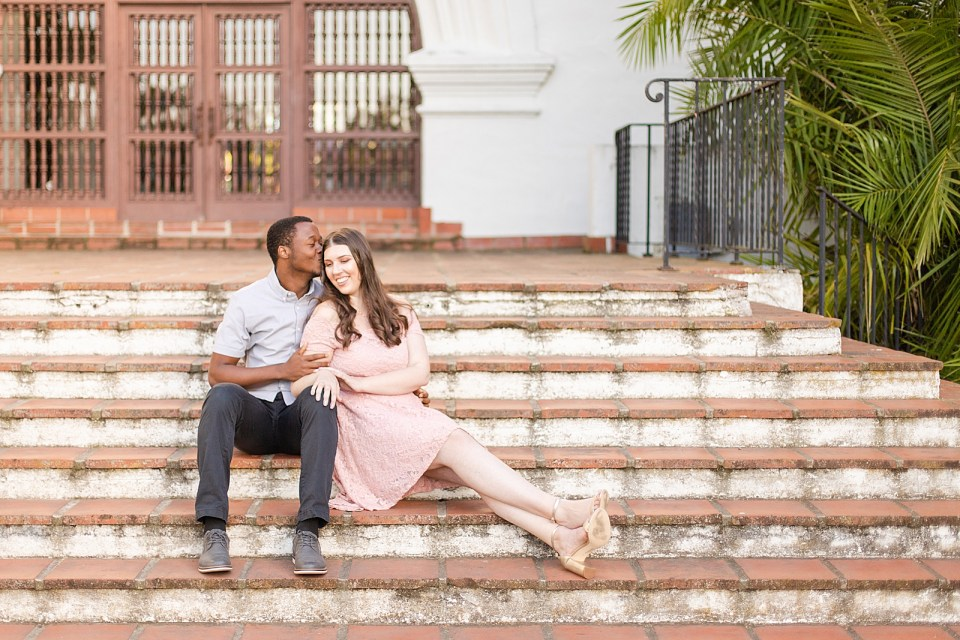Sarah leaning against Myles and smiling as Myles kisses her forehead while they are sitting on the steps of the Courthouse during their Alice Keck Garden Engagement session.