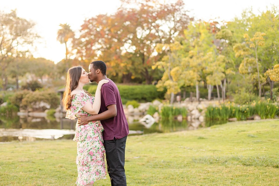 The couple is sharing a kiss with the pond in the background during their Alice Keck Garden Engagement session