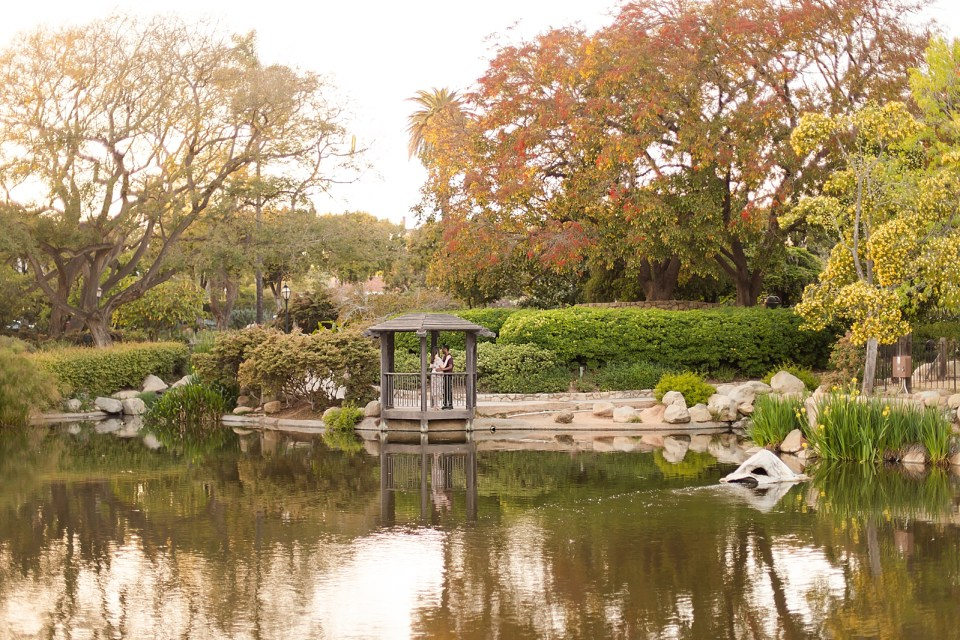 A landscape photo of Sarah & Myles standing in the gazebo from across the pond.