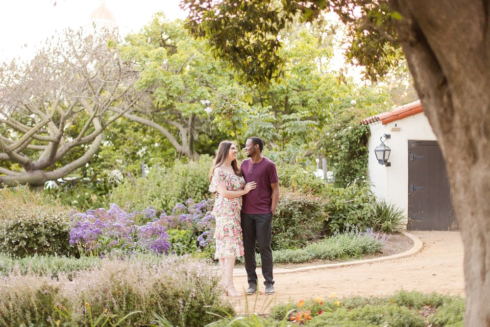 Sarah & Myles sharing an intimate moment during their Alice Keck Garden Engagement session. There is a white house and tons of green trees in the background.