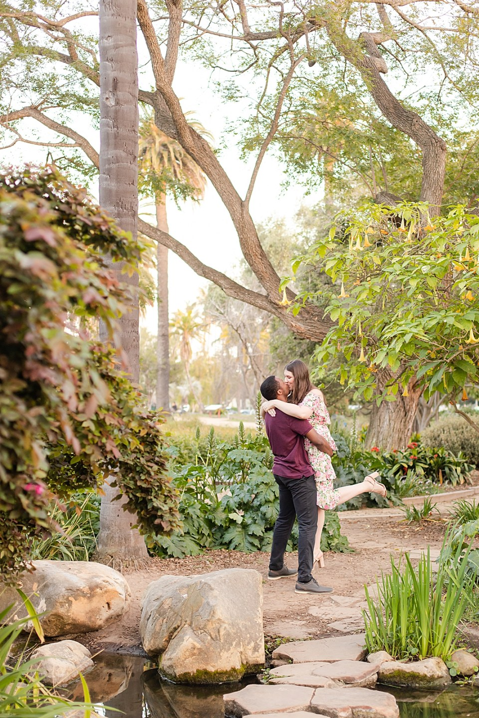 Myles lifting Sarah up and giving her a kiss with trees in the foreground and background during their Alice Keck Garden Engagement session.
