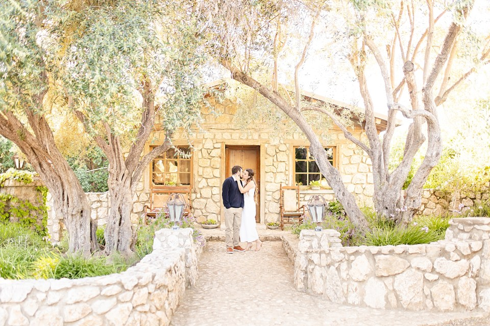 The couple sharing a kiss in front of the Bridal Suite during their Whispering Rose Ranch Engagement Session