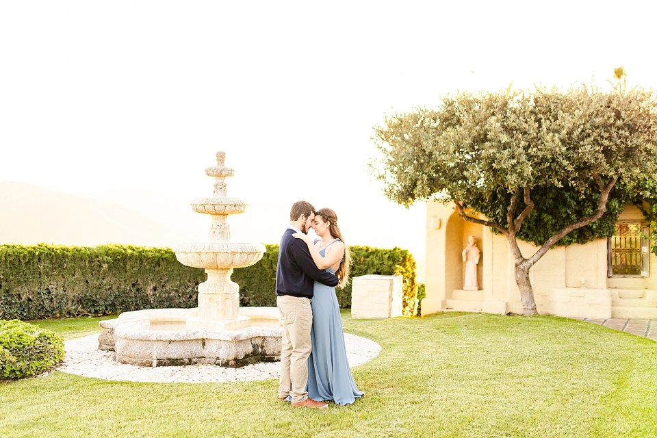 The couple touching their foreheads together in front of a fountain with the mountains and sun setting in the background.