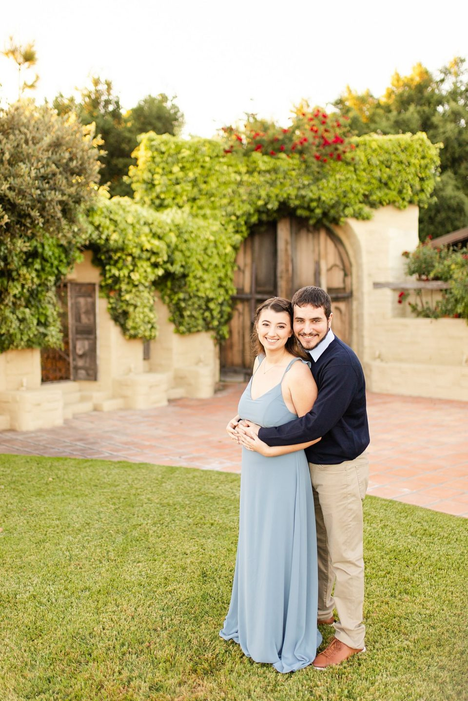 The couple smiling at the camera with the antique doors behind them during their Whispering Rose Ranch Engagement Session
