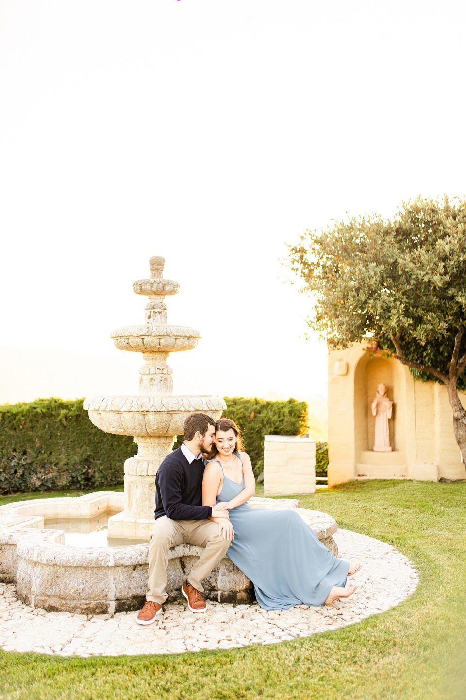 The couple sitting on the fountain. Sofia is leaning up against Joey and holding his hands.