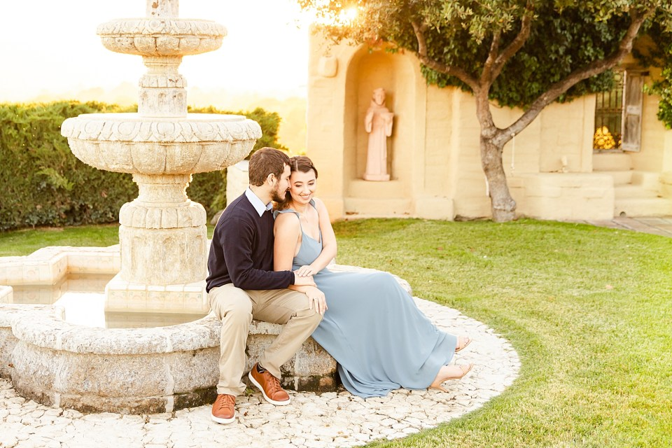 Joey is giving Sofia a kiss as she smiles at the ground in front of her while they sit on the fountain during their Whispering Rose Ranch Engagement Session
