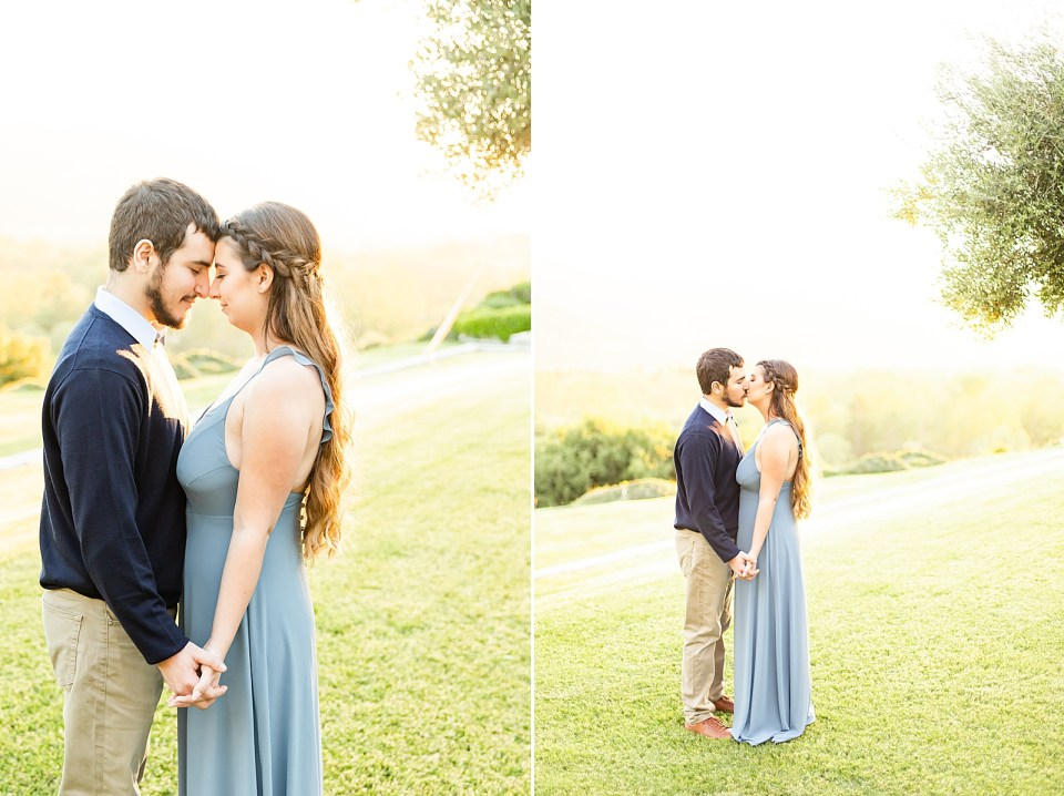 The couple touching foreheads and holding hands down low with the sunset in the background and rolling grassy lawns.