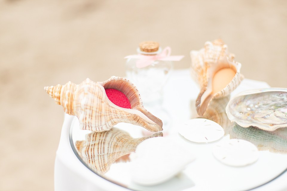 Two sea shells filled with red sand in one and yellow sand in the other on a mirrored table next to sand dollars and a glass bottle in the shape of a heart.
