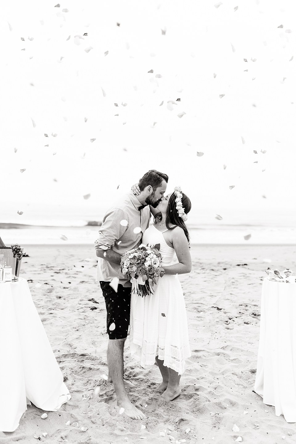 A black and white photo of the couple sharing a kiss while flower petals fall around them during their Santa Claus Beach Elopement