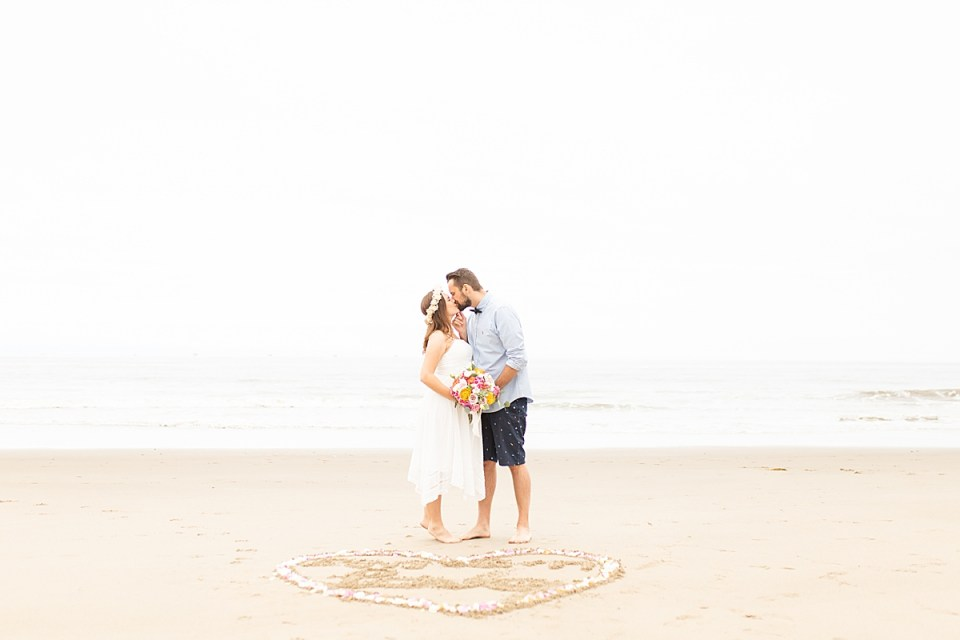 Gina & Michael kissing and holding her bouquet together. Below them is a heart drawn in the sand with flower petals along the edges.