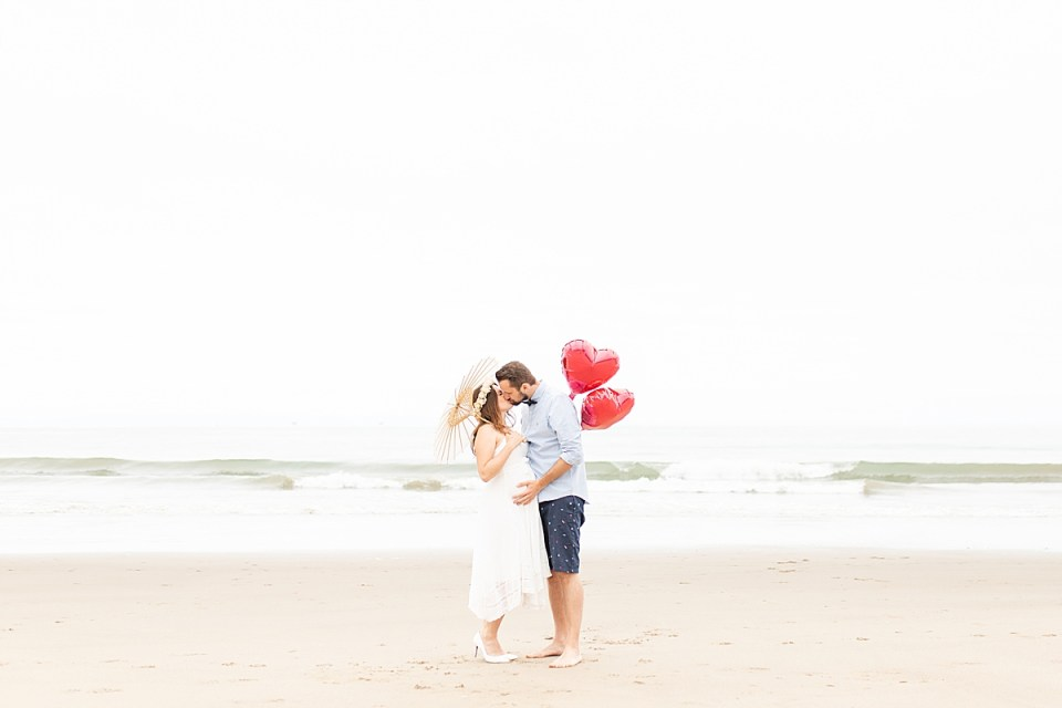 Gina & Michael sharing a kiss with the ocean waves behind them. She is holding an umbrella and he is holding red, heart-shaped balloons during their Santa Claus Beach Elopement