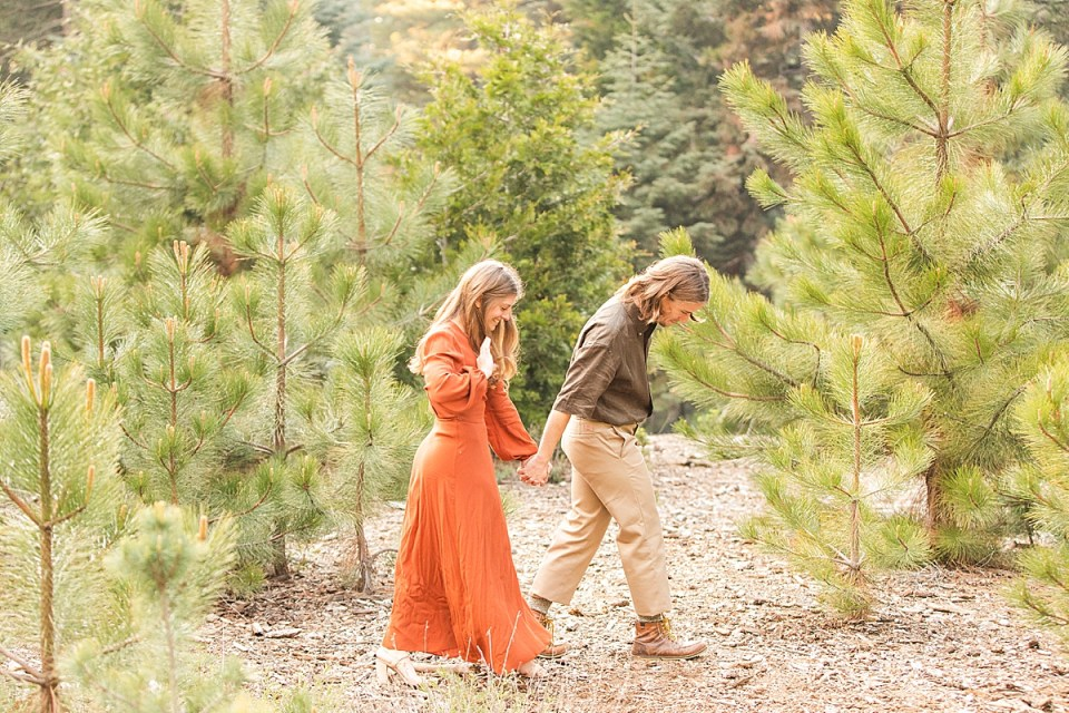 Abby running her fingers through her hair as Rothwell leads her by the hand further into the forest during their Lake Arrowhead Engagement session