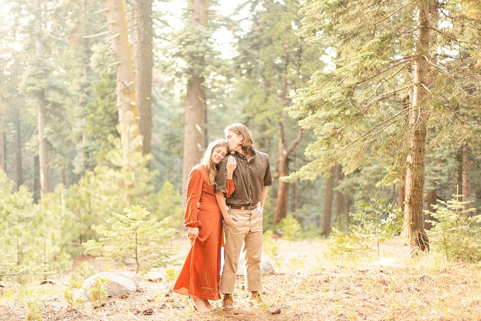 A wide photo of the couple cuddling together with the large pine trees behind them.