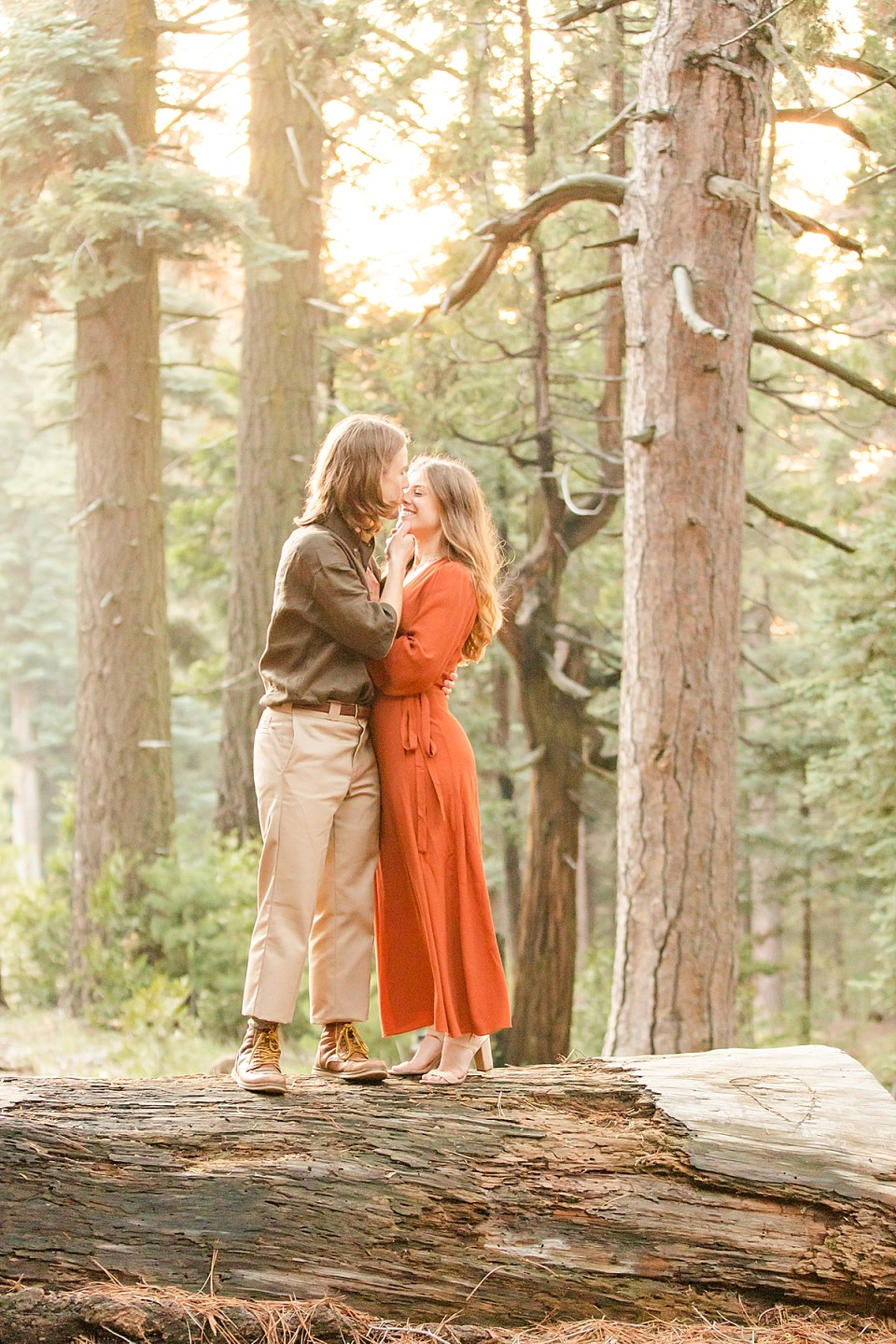 Rothwell pulling his fiancé in close with his arm around her waist and his other hand pulling her chin in for a kiss. Abby is standing on the tips of her toes to give Rothwell a kiss during their Lake Arrowhead Engagement session.