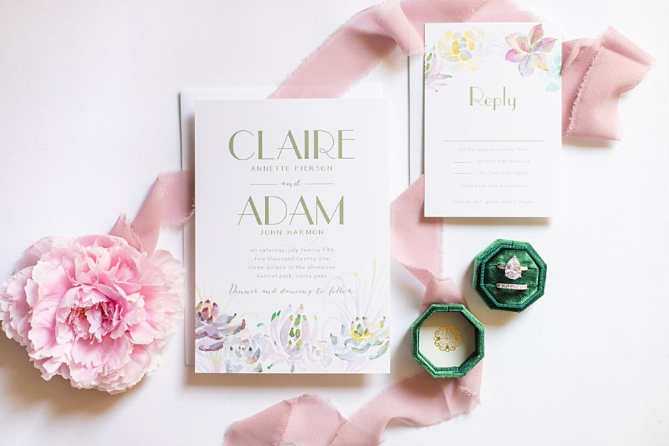 A pink peony with blush lace scattered around bridal shower brunch invitations.