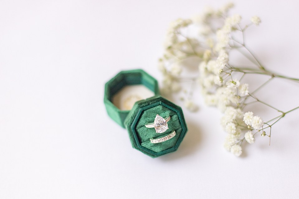 Emerald green ring box with engagement ring and bride's wedding band next to some Baby's Breath flowers.