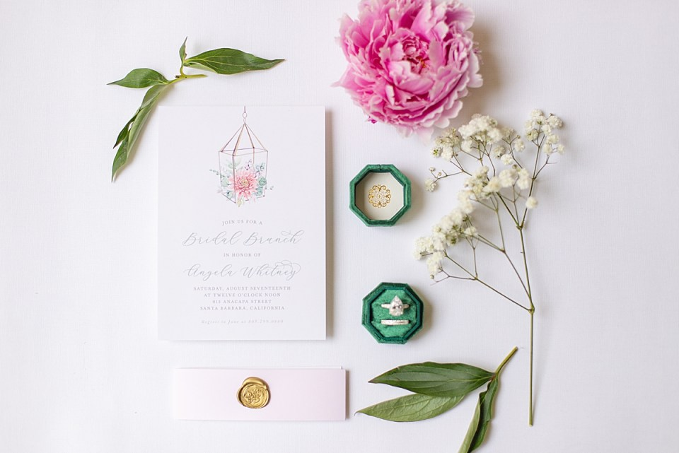 bridal shower brunch invitations with a emerald green ring box and engagement ring and wedding band inside. As well as florals and greenery.