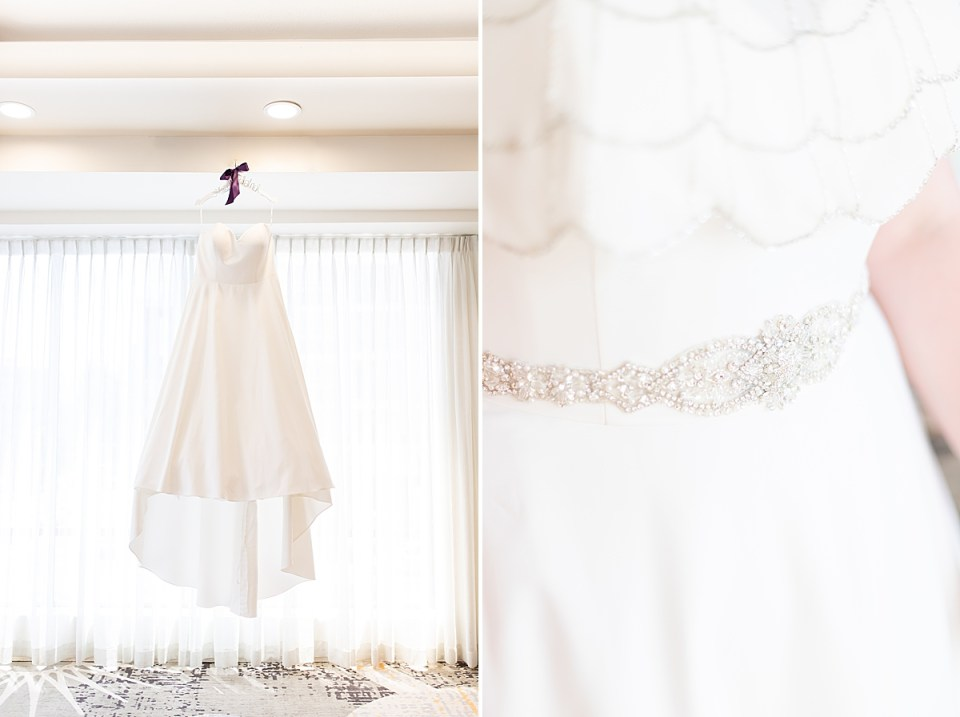 The bride's dress hanging by a window and a close up of the bride's belt sparkling in the light during the couples Brandview Ballroom wedding.