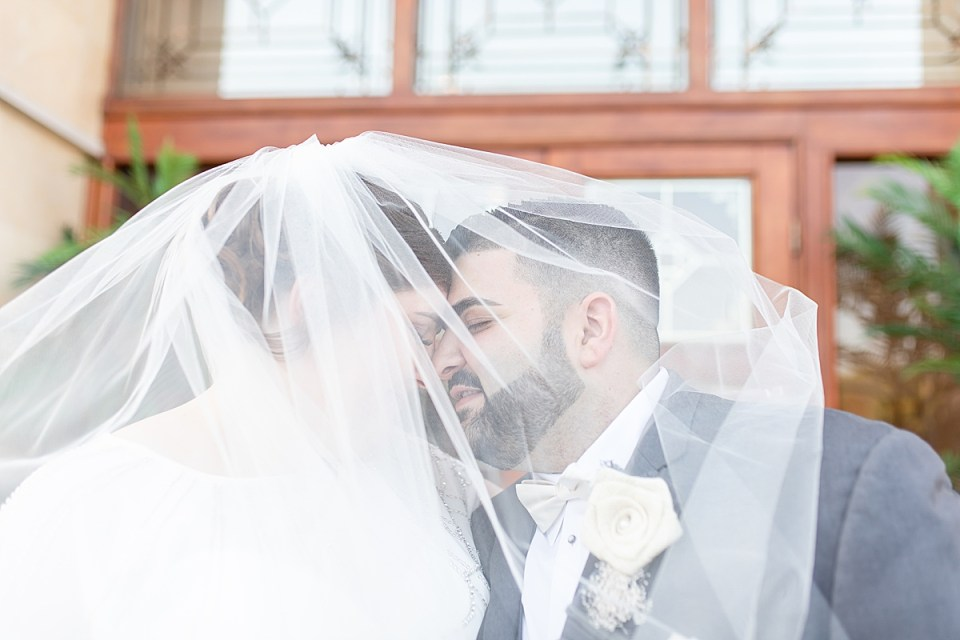 The bride and groom under her veil forehead to forehead outside their wedding venue.