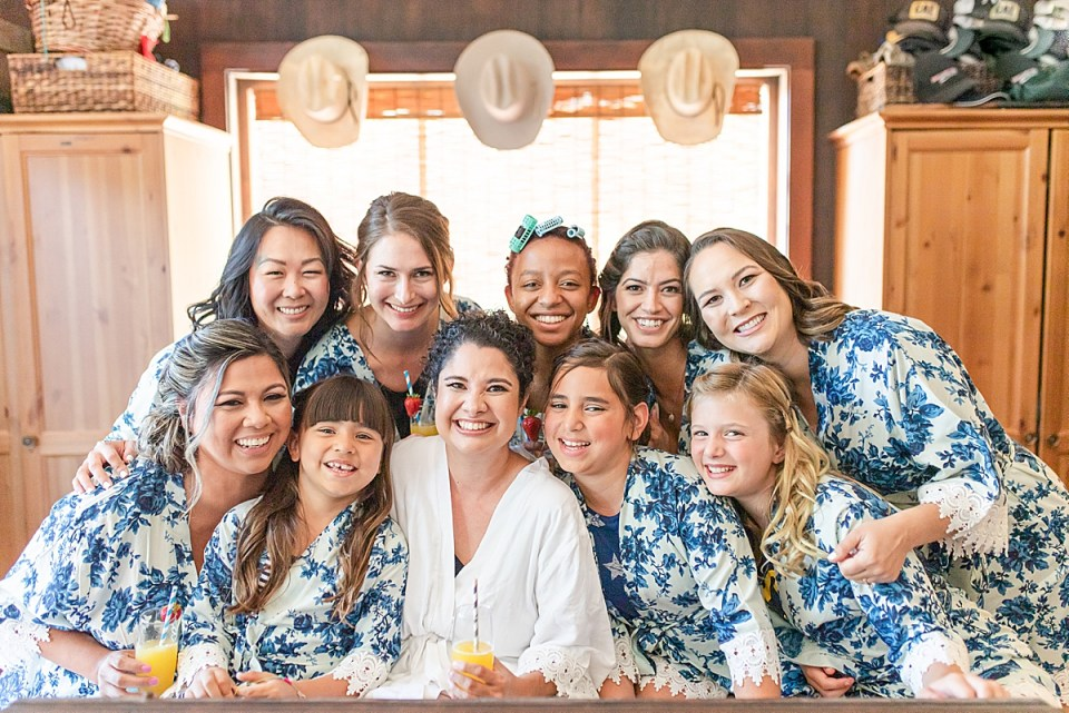 Brandi and all of her bridesmaids and jr. bridesmaids on the bed in her getting ready room.
