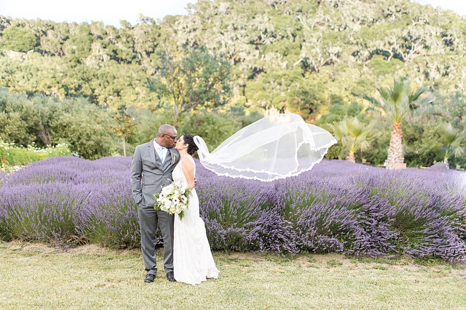 Brandi holding her bouquet and sharing a kiss with Victor in front of the rolling hills and lavender field.