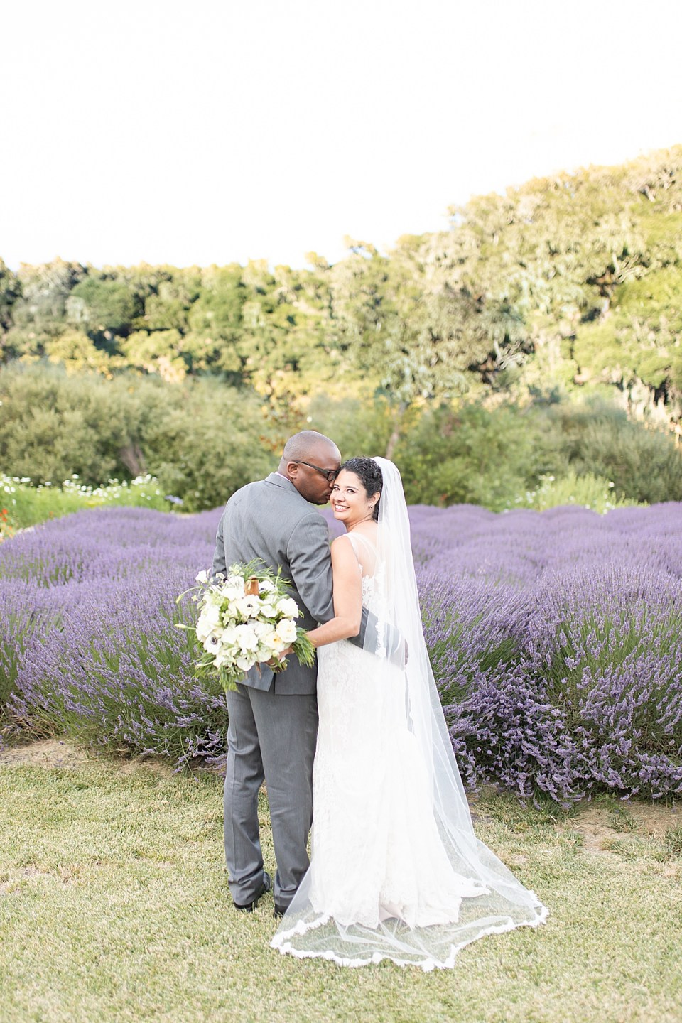 Brandi smiling back at the camera and Victor smiling at his bride in front of the lavender fields.