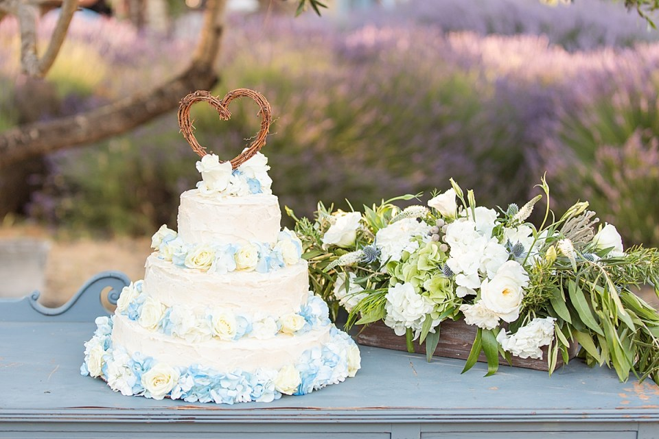 The couples cake next to some greenery and white roses.