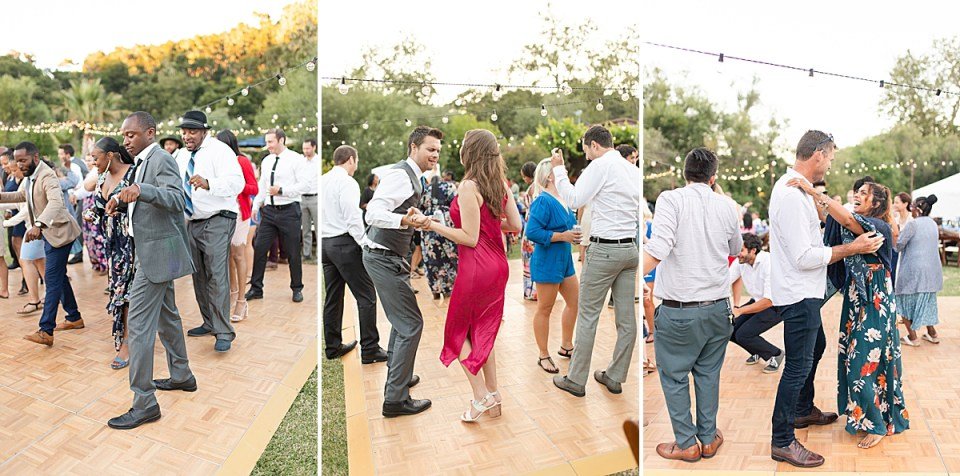 guests at this couple's wedding dancing on the dance floor with string lights hanging above them