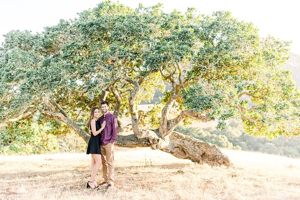 The couple is standing near an oak tree during their San Luis Obispo Bishop's Peak engagement session