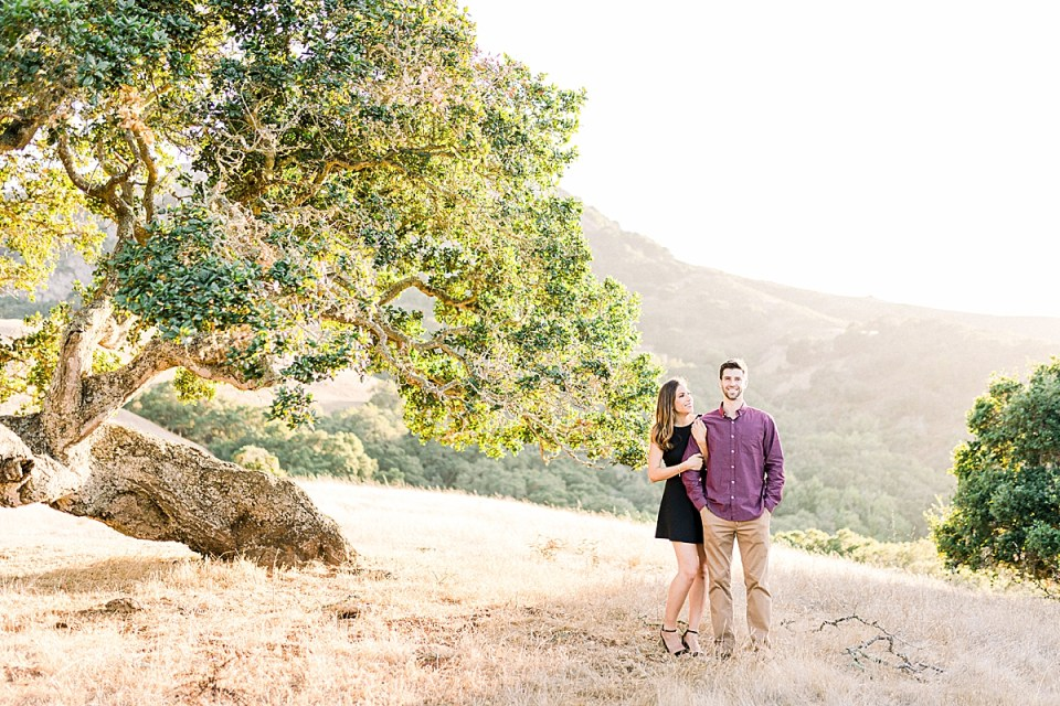 Kat smiling at Brett while Brett looks at the camera as they stand near an oak tree during their San Luis Obispo Bishop's Peak engagement session
