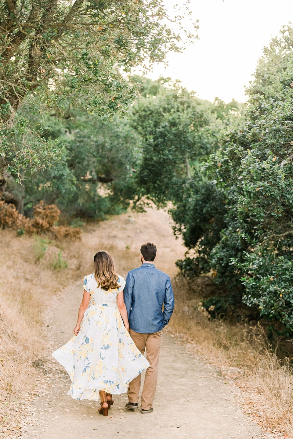 The couple walking under multiple oak trees and their branches during their Bishop's Peak engagement session.