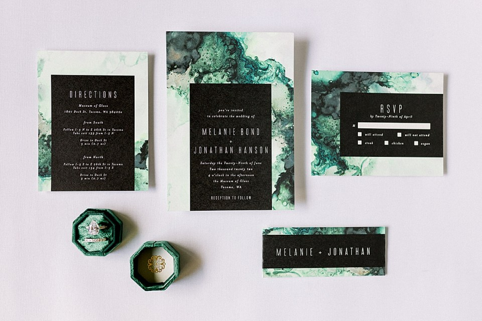 Green and black Wedding Invitations with the bride's engagement ring and wedding band in a green ring box.