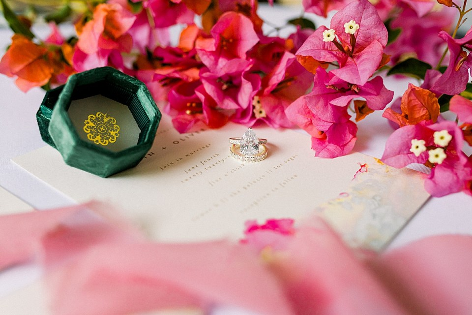 The bride's engagement ring sitting on top of her wedding band place diagonally on the Wedding Invitations with flowers behind and pink lace in the foreground.