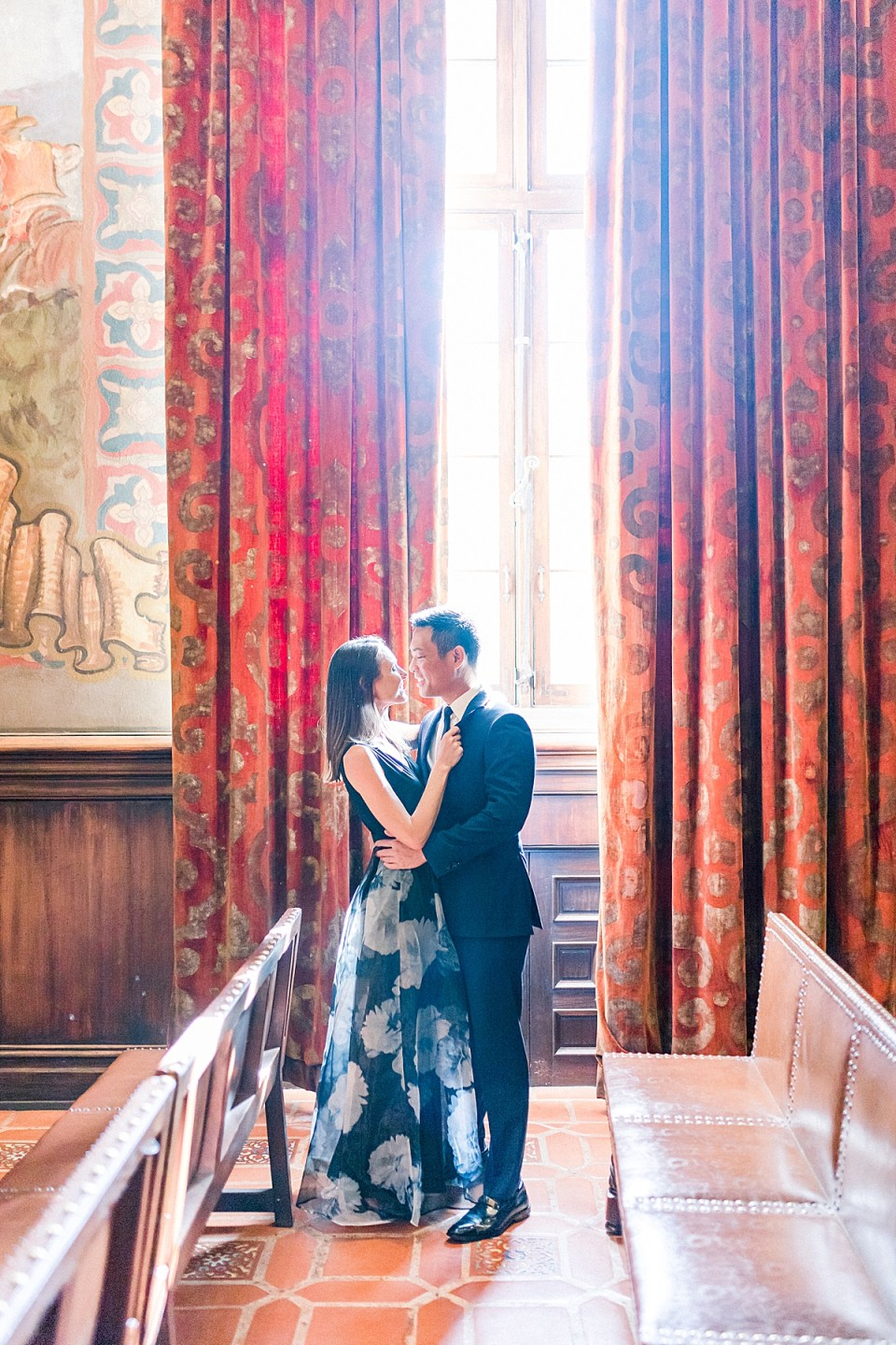 The couple smiling into each others eyes while standing in the light coming in from the window through the Mural Room at the Santa Barbara Courthouse.
