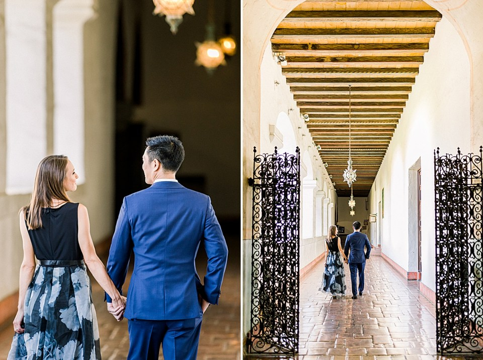 The couple holding hands as they walk away from the camera down a hallway with chandeliers above them. A second image pulled back of the couple walking down the hallway.
