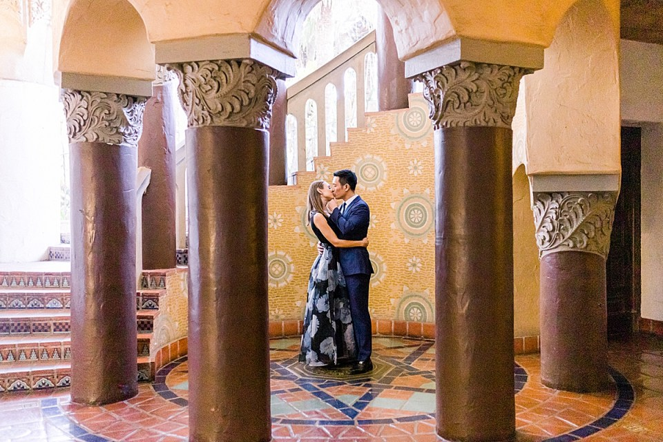 The couple sharing a kiss in the middle of the spiral staircase at the Santa Barbara Courthouse in Santa Barbara, California.