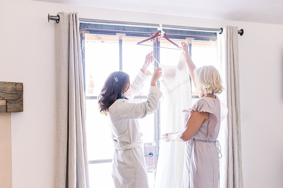 The bride and her mother taking the wedding gown off the hanger so she can put it on.