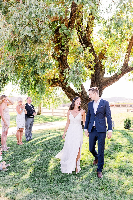 Lauren & Scott walking down the aisle holding hands while their families look on during their San Luis Obispo Farm Wedding