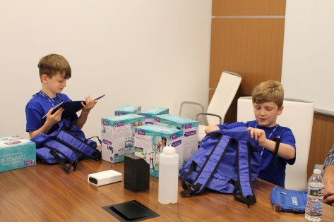 Matthew and Karson Lloyd happily sort through their Grifols swag bags.