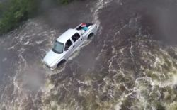 A US Coast Guard helicopter checks on a pickup truck surrounded by water.