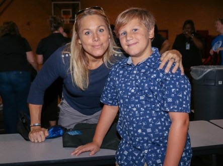 JCPS West Johnston area school social worker Whitney Kelbaugh and her son Rylan Kellis pack book bags that will be delivered to Johnston County Public Schools students.