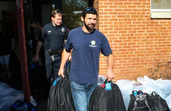 Members of the Fraternal Order of Police, Brian O'Branovich and Robert Stewart both members of the Smithfield Police Department, help carry book bags out to cars to be transported to Johnston County Public Schools.