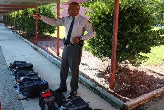 Highway Patrol First Sgt. Derek Mobley directs teachers and officers on where to place book bags.