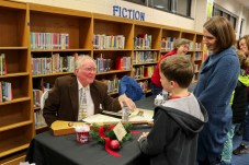 Local author Shelby Stephenson (left) talks with Pine Level Elementary student Wilmond Barnes (center) and West Clayton Elementary Principal Paige Barnes (right) at the JOCO Reads event.