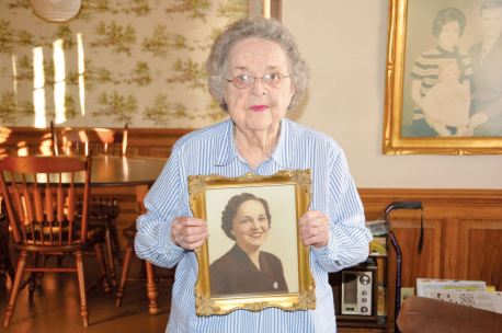 Lillington' s Helen Byrd is shown here with a picture of herself from the 1940s. Mrs. Byrd celebrated turning 100 years old Saturday during a celebration at the Atkins House in Lillington.